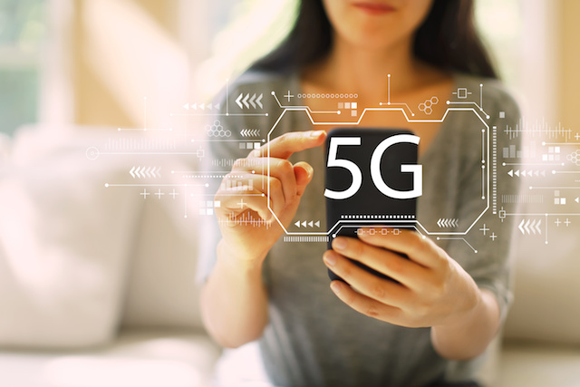 5G network with woman using her smartphone in a living room